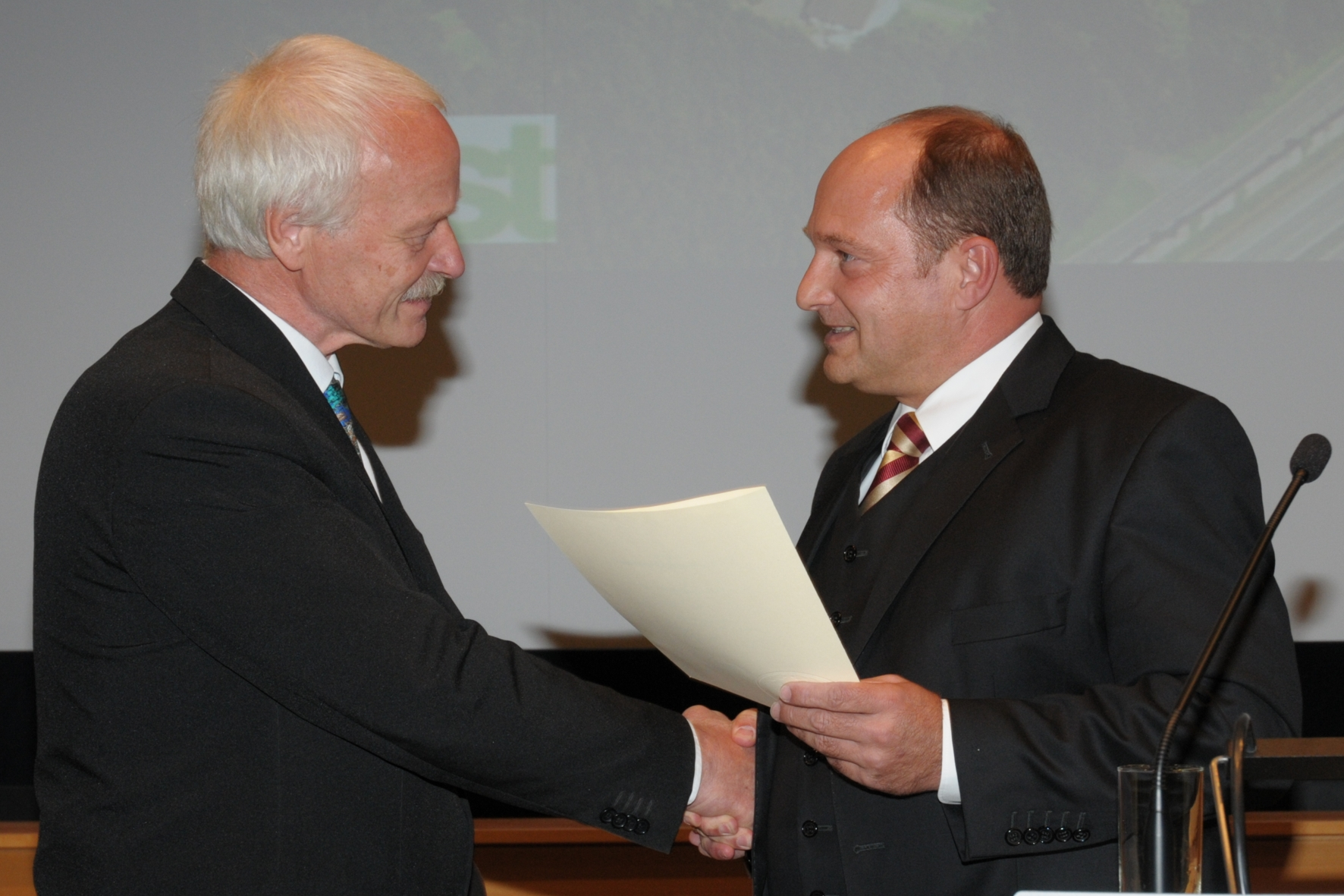 Dr. Peter Reichelt gets the official document of his retirement from State Secretary Rainer Bomba